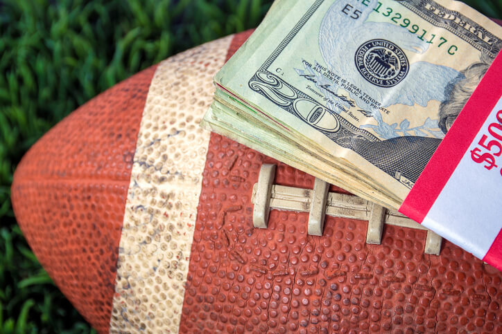 close up of wrapped money stack on football and green grass background